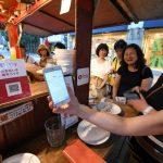 屋台でスマホを使い決済する女性客(福岡市中央区の「レミさんち」)